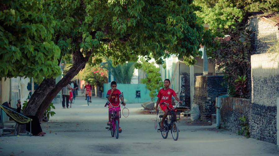 Children riding bicycles on Maldives local island
